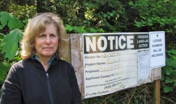 "Barbara Ingram stands in front of the site of a proposed development in her neighborhood. Snohomish County denied the permit for the development due to ""slope stability and drainage issues"" but the developer has reapplied."