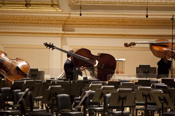 The double bass section files in. The orchestra was formerly known as the Simón Bolívar Youth Orchestra. The musicians, and Gustavo Dudamel himself, are products of the El Sistema music education program in their native Venezuela.
