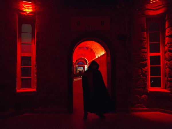 "An actor looms in the prison's rotunda during the haunt. ""Terror Behind The Walls"" sets are constructed in a way where it does not damage the prison's structure and can quickly be removed."