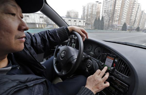 A taxi driver uses Didi, another cab-hailing app, to find customers in Beijing on Feb. 18.