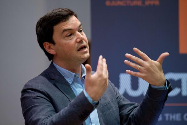 "French economist Thomas Piketty, pictured here during a presentation at King's College in London on April 30, is drawing criticism and praise for his new book ""Capitalism in the Twenty-First Century,"" in which he argues that capitalism leads to the concentration of wealth in the hands of those already rich. (Leon Neal/AFP/Getty Images)"