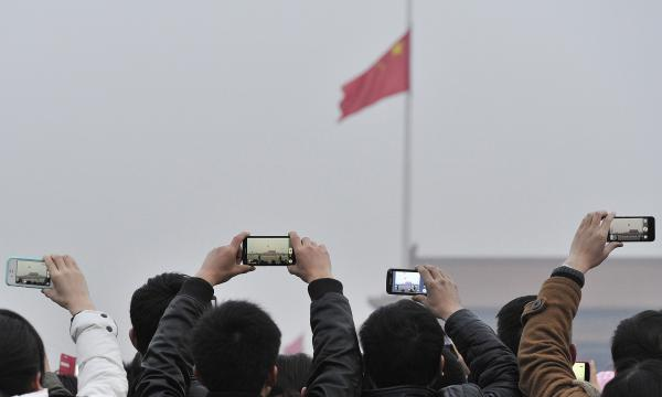 Visitors use their cellphones to record the daily flag-raising ceremony in Tiananmen Square in Beijing on March 3.