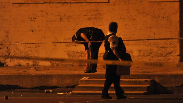 Chicago police detectives investigate the scene where a number of people, including a 3-year-old child, were shot in a city park in Chicago in 2013.