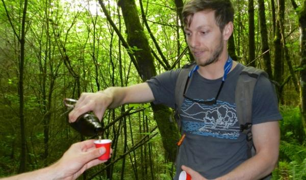 On a recent hike, brewer Dan Hynes pours samples of beer he made using yeast collected from an old growth forest near Portland.