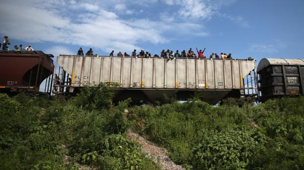 Migrants arrive at a rest stop in Ixtepec, Mexico, after a 15-hour ride atop a freight train headed north toward the U.S. border on Aug. 4. Thousands of migrants ride atop the trains, known as <em>La Bestia,</em> or The Beast, during their long and perilous journey through Mexico to the U.S.