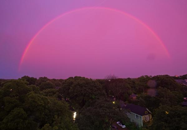 The sky turns pink as a rainbow appears at dusk over the suburbs during a thunderstorm on Thursday.