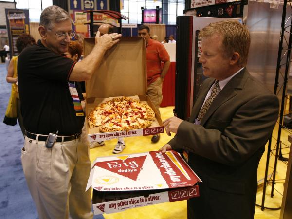 Patrick McCoy (right) and Harry Fowler of Schwan's Food Service show off their company's Big Daddy's pizza at the School Nutrition Association's national conference in Chicago in 2007.
