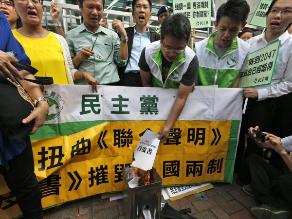 "Protesters burn a mock ""white paper"" released by China's State Council on Tuesday, which says Beijing holds ultimate control over the former British colony."