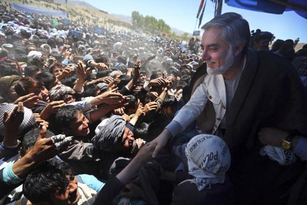 Abdullah Abdullah shakes hands with supporters at an election campaign rally in Ghor province. He'll face off Saturday against former Finance Minister Ashraf Ghani.