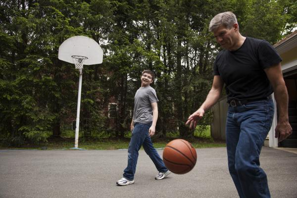 Ed Damiano and his son David,  15, play basketball at home in Acton, Mass. Ed has invented a device he hopes will make David's diabetes easier to manage.
