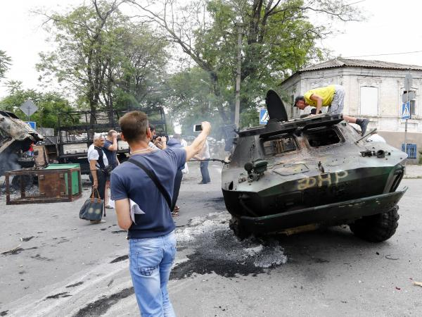 Local residents examine  destroyed vehicles at the site of fighting after Ukrainian forces recaptured the city from pro-Russian separatists on Friday.