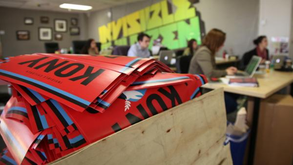 "A box brims with ""Kony 2012"" posters at Invisible Children offices in March 2012. The group had to increase staff after the success of the film, but now it has a budget problem."
