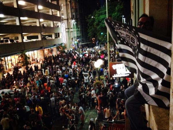 Spurs fans congregate on Commerce Street between South Alamo and N. Presa following the end of game five. Fan Maury Vasquez holds a flag from a balcony window.