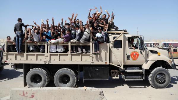 Iraqi men flash victory signs as they leave the main recruiting center to join the Iraqi army in Baghdad on Tuesday.