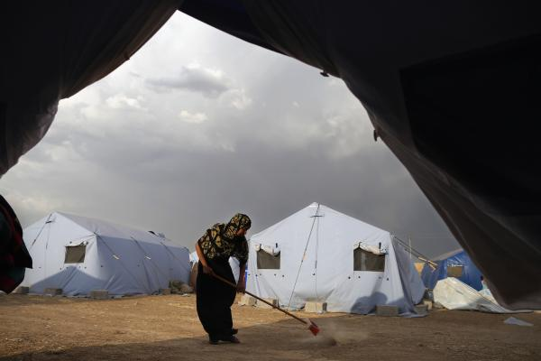 A woman sweeps outside her tent at a camp set up next to a Kurdish checkpoint in Kalak, Iraq, on Friday. The Kurdish Regional Government has set up four such camps, as Iraqis fleeing the areas overrun by ISIS and other Sunni extremists hope to enter the safety of the Kurdish region.