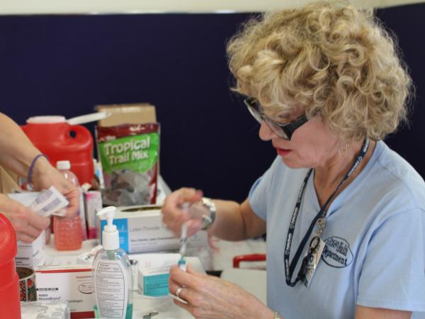 Jacqueline Fletcher readies a measles vaccine to give at a makeshift clinic in central Ohio. About 8,000 Amish people in the area have received measles vaccinations since April.
