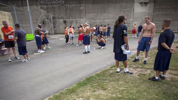 Runners chat at a recent track event at the Oregon State Penitentiary in Salem. The prison's program allows inmates (in blue shirts) to run alongside regular citizens (in orange).