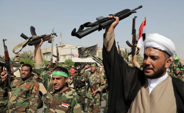 Volunteers of a newly formed Shiite militia chant slogans against Sunni militants of the Islamic State of Iraq and Syria, or ISIS, during a parade in the Shiite stronghold of Sadr City in Baghdad on Saturday. Even as these Shiite fighters are answering the call to arms to fight ISIS, many of them do not support the country's Shiite prime minister, Nouri al-Maliki.