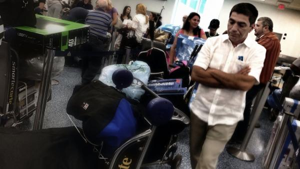 A man stands in line at Miami International airport to board a charter flight to Havana, Cuba. Travelers often fly to Cuba from the U.S. with piles of goods, despite a decades-long trade embargo.
