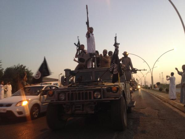 Fighters of the Islamic State of Iraq and Syria parade in a commandeered Iraqi security forces armored vehicle in Mosul, Iraq, on June 23. Human Rights Watch says the group executed at least 160 unarmed Iraqis after it took control of the city of Tikrit.
