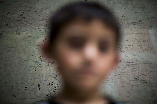 A child deported from the United State poses for photo in front of a map of Guatemala City at an immigration shelter in Guatemala City on June 19.