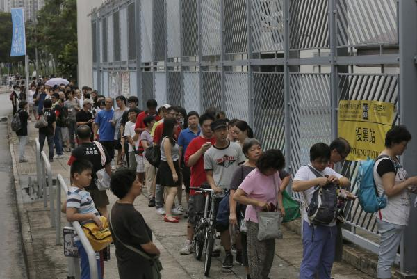People queue at a polling center to vote in an unofficial referendum on democratic reform in Hong Kong on Sunday, June 22, 2014.