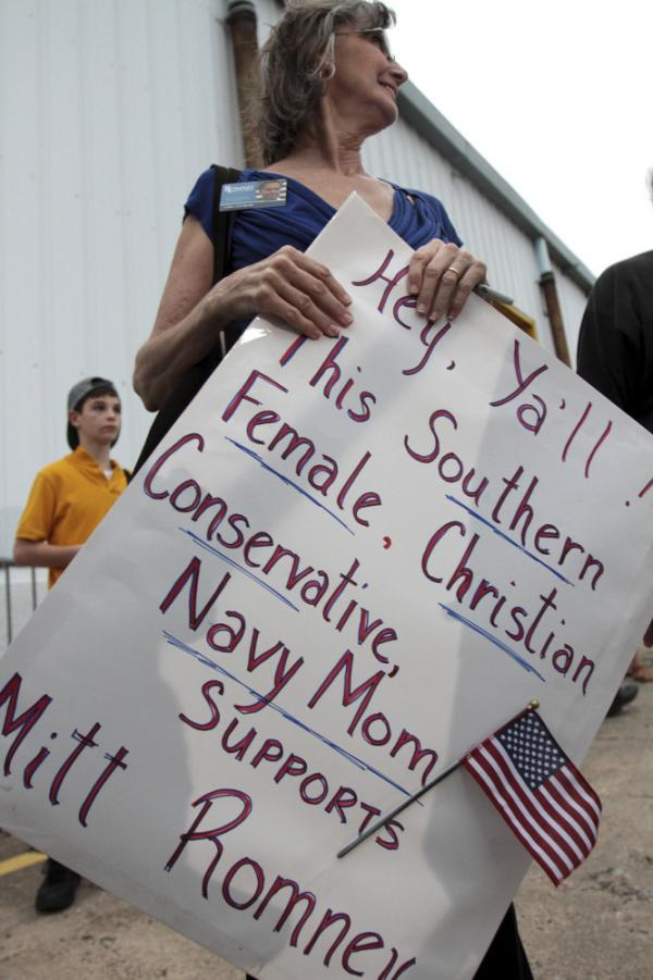 Carla Castorina of Hurley, Miss., holds a sign supporting former Massachusetts Gov. Mitt Romney after a campaign rally at the Port of Pascagoula in Pascagoula, Miss., on March 8. Polls show a tight race in the state, which holds its primary on Tuesday.