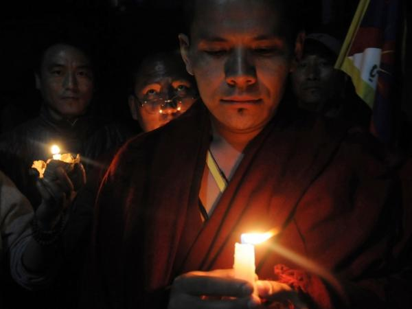 A Tibetan Buddhist monk holds up a candle with other Tibetan exiles during a candlelight vigil for Tibetan Janphel Yeshi, who set himself on fire earlier in New Delhi.