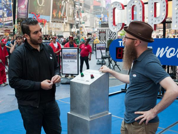 Artist Steve Lambert, right, asks people to vote on whether capitalism is working — for them. The art installation is in Times Square through Oct. 9.