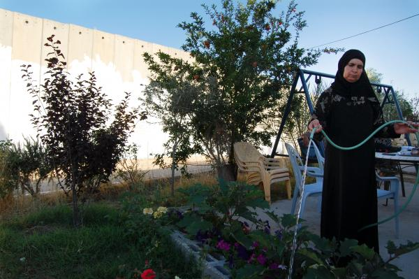 Ishaq's mother waters plants in the family's garden. The family lost a nursery business to the barrier, but have planted a few fruit trees and flowers.