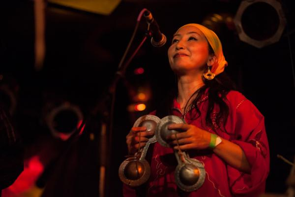 Percussionist and vocalist Chikako Iwahori plays the small brass castanet-like instruments called the <em>qarqabat</em> during Hassan Hakmoun's set.
