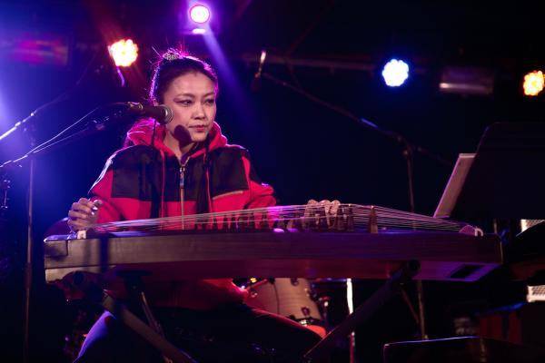 Chinese artist Wu Fei sings and plays the <em>guzheng</em>, a traditional zither, in the trio.