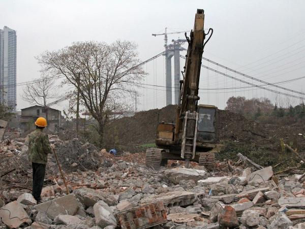 Parts of Wuhan seem like an open construction site. Here, heavy machinery clears the way for a river drive while construction continues on a bridge across the Yangtze River.