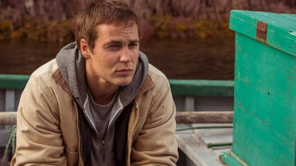 Taylor Kitsch plays Paul Lewis, a doctor in demand, in <em>The Grand Seduction</em>. It's a classic tale of an outsider discovering the appeal of a small town — except the rustic charm is manufactured for Lewis' benefit.