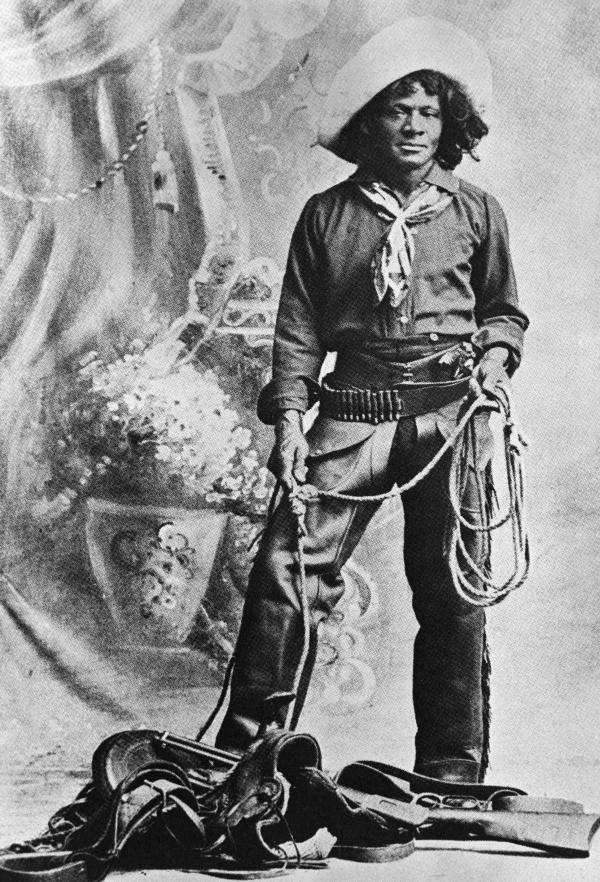 Nat Love, African American cowboy who claimed to have won the name of Deadwood Dick in South Dakota, 1876, by virtue of his roping talent. Full length photo with lariat and saddle. From his privately published autobiography (1907).