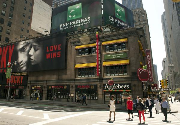 A BNP Paribas advertisement sits atop a building on Broadway June 2 in New York. BNP Paribas faces a potential fine of up to $10 billion USD for breaking sanctions imposed by the U.S. government on Iran. The fine would be the largest imposed on a bank by US. regulators for sanctions-breaking, and one of the largest regulatory fines in history. (Don Emmert/AFP/Getty Images)