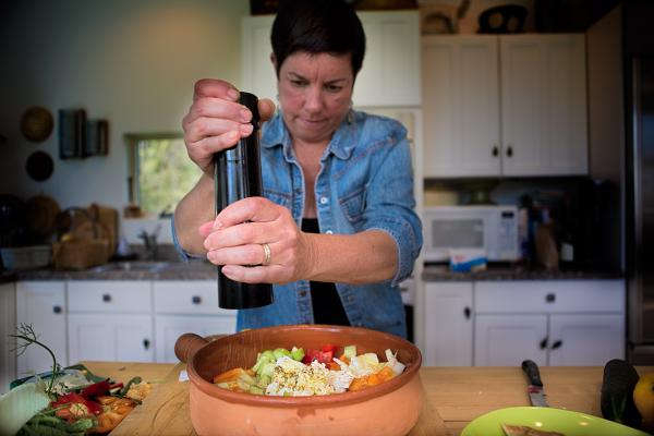 Kathy adds cracked black pepper after adding lemon juice and olive oil. (Jesse Costa/WBUR)