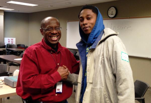 Alphonso Pettis (left) instructs a fatherhood program at the Milwaukee group, Next Door. Darnell Reid (right) is one of the participants. (Erin Toner)