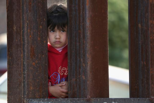 A child on the Mexican side of the U.S.-Mexico border fence looks into Arizona during a special 'Mass on the Border' on April 1, 2014 in Nogales, Arizona. (John Moore/Getty Images)