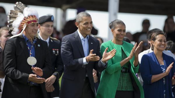 President Barack Obama, first lady Michelle Obama, and Standing Rock Sioux Tribal Nation Chairman Dave Archambault II, left, and his wife Nicole Archambault, right, applaud as they watch a Cannon Ball flag day celebration, at the Cannon Ball powwow grounds in Cannon Ball, N.D., on June 13.