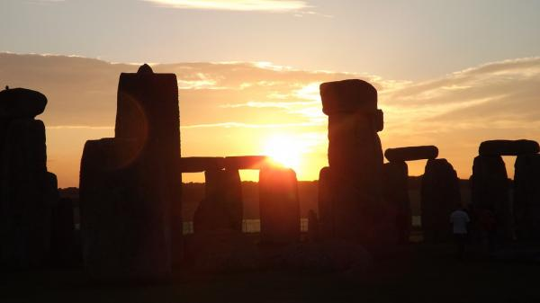 The midsummer sun rises over Stonehenge.