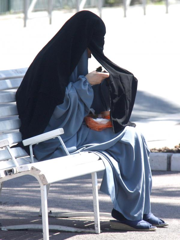A woman wearing a niqab eats on the Promenade des Anglais in Nice, France, on June 26, 2012. The European Court of Human Rights on Tuesday upheld a French law that bans face-concealing veils in public places.