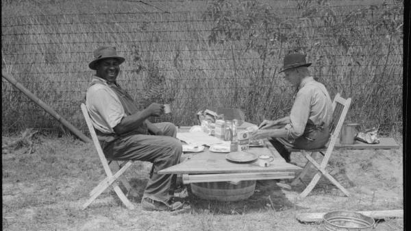 A stable hand and a trainer eat a picnic lunch before the Shelby County Horse Show and Fair, Shelbyville, Ky.