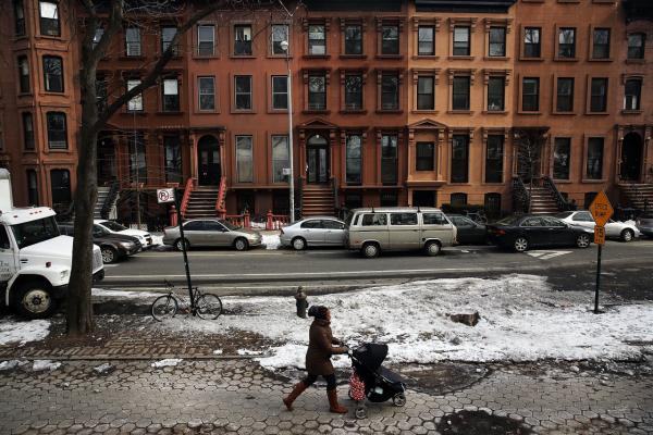 A woman and child walk down a street in the Fort Greene neighborhood on February 27, 2014. Numerous Brooklyn neighborhoods, which were once considered dangerous and underdeveloped, have gone through transformations in recent years resulting in more affluent newcomers displacing long time residents. (Spencer Platt/Getty Images)