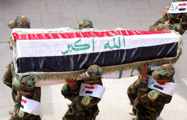 The coffin of an Iraqi fighter, who reportedly died fighting with the al-Haq militia alongside government forces, is carried prior to burial in Najaf this March. Najaf's clerics have called for more Shiites to take up arms.