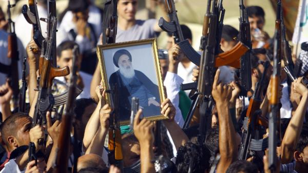 Iraqi Shiites in Najaf brandish their weapons and a poster of the Grand Ayatollah Ali al-Sistani, who broke with Iraqi tradition and called on Shiites to fight the current insurgency.