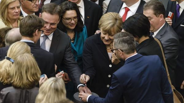 German Labor and Social Affairs Minister Andrea Nahles (center) and Chancellor Angela Merkel (right) cast their votes for a national minimum wage Thursday. The legislation sets a requirement of more than $11.50 in hourly pay.