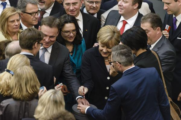 German Labour and Social Affairs Minister Andrea Nahles (C) and German Chancellor Angela Merkel (C, R) cast their ballot during a vote on a bill for a national minimum wage on July 3 in Berlin. (Clemens Bilan/AFP Photo)