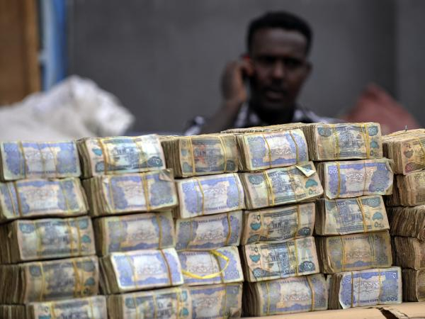 A money changer sits behind piles of banknotes in Hargeisa in Somaliland, an autonomous, relatively peaceful region in northern Somalia. The self-declared nation of Somaliland, like Somalia itself, lacks a formal banking system, and residents rely on <em>hawaladars</em> to receive money from abroad.