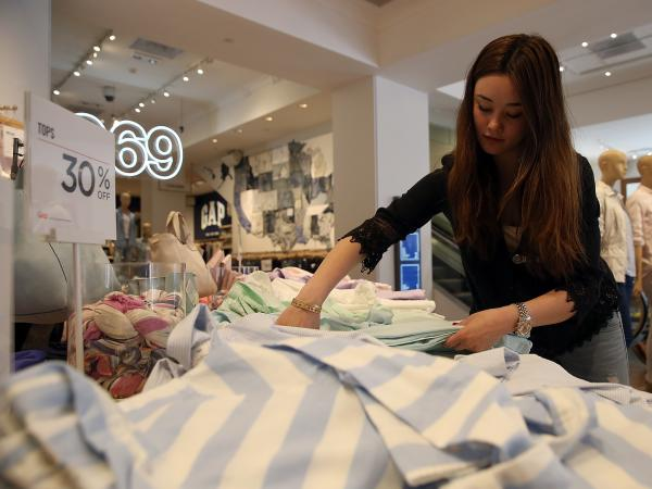 A Gap employee works at a store in San Francisco. The company plans to raise its minimum wage in phases to $10 an hour by next year.
